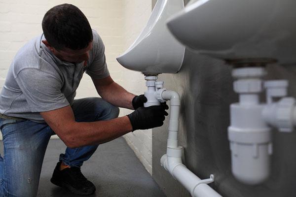 plombier débouche une canalisation WC