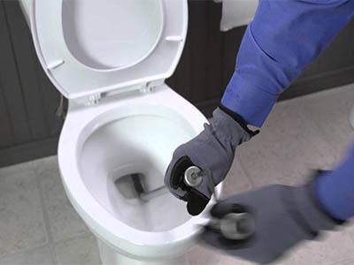Débouchage canalisation WC avec un furet déboucheur à manivelle